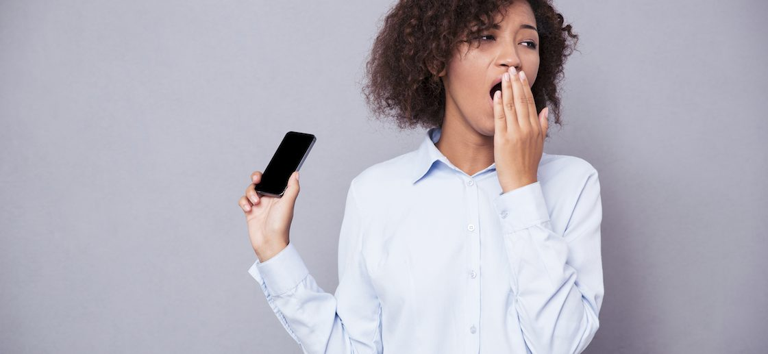 Portrait of afro american woman yawning while holding smartphone on gray background